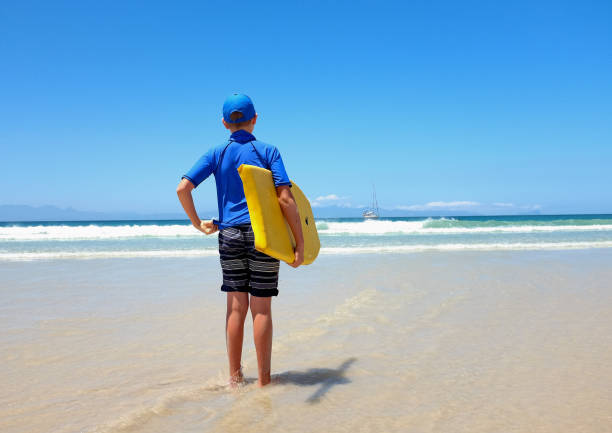 Backview of boy with bodyboard on beach with no surf! stock photo