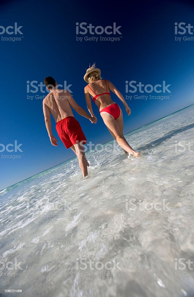 Backview of Couple Walking Along The Beach Holding Hands royalty-free stock photo