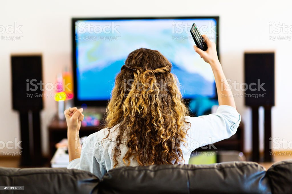 Backview of curly-haired girl waving and cheering TV broadcast stock photo