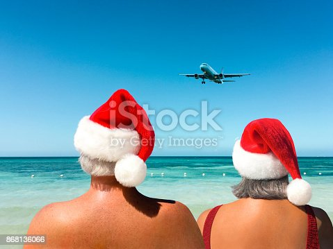Backview of Man & Woman Wearing Santa Hat on a Tropical Beach