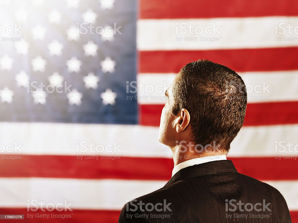 Backview of politician or businessman looking at US national flag stock photo
