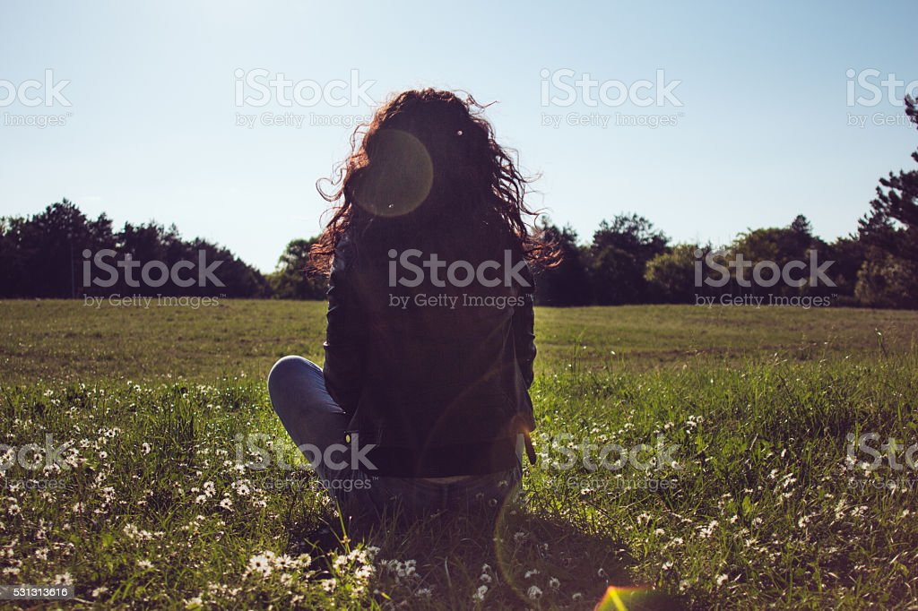 Backview of young brunette girl among flowered meadow. stock photo