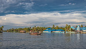 blue church on the edge of alleppey backwater with houseboats trail and palm tree giving the real feeling of nature with God.