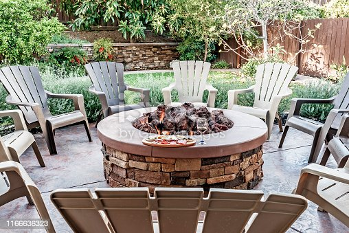 Large outdoor fire pit surrounded by wooden rocking chairs, beautifully landscaped backyard, with the glass of wine and food platter.