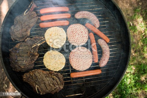 Various meat choices on black circular charcoal grill