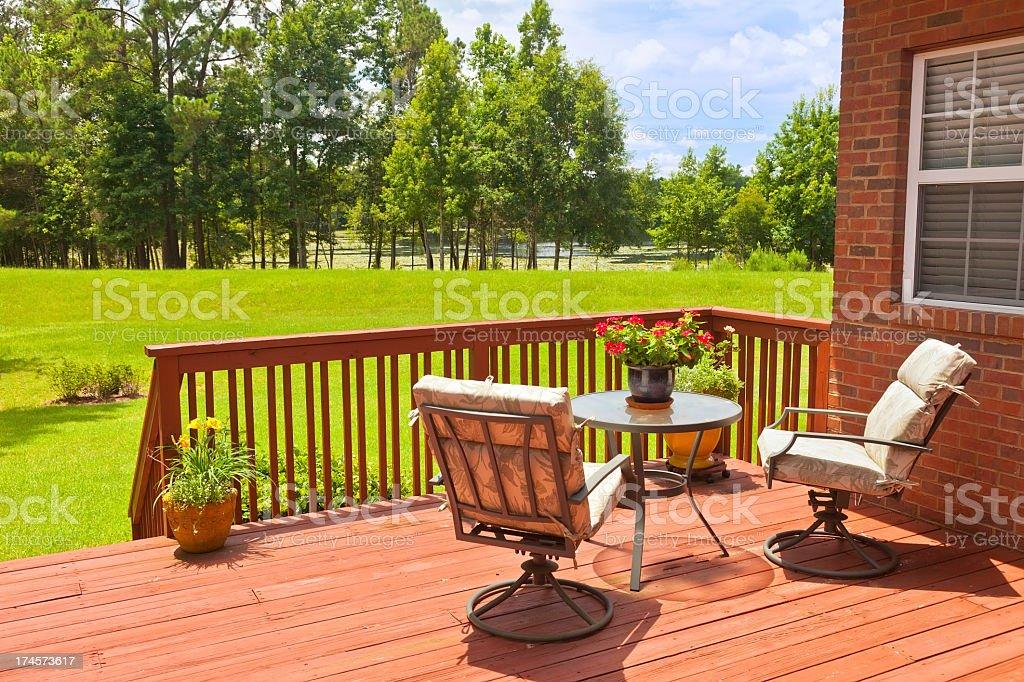 Backyard deck next to a green field stock photo