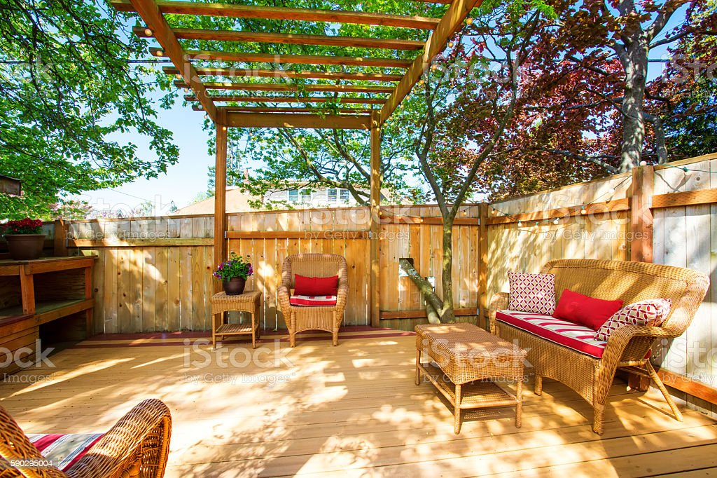 Backyard deck with wicker furniture and pergola. royaltyfri bildbanksbilder
