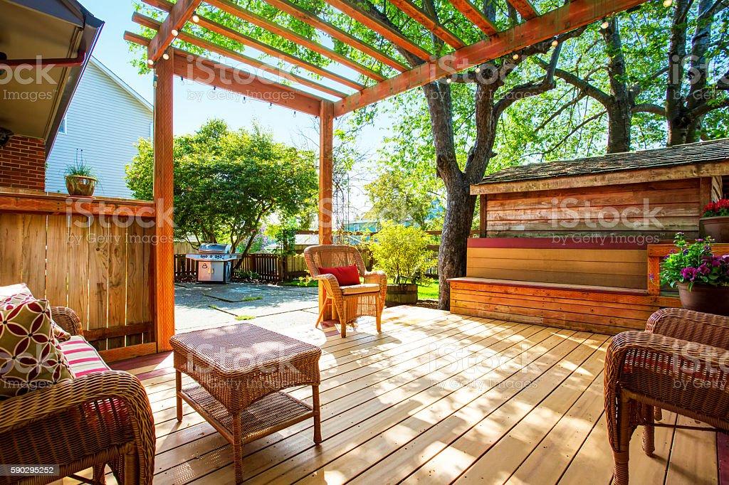 Backyard deck with wicker furniture and pergola. Стоковые фото Стоковая фотография