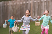 Children participate in Easter games in a residential, fenced-in backyard. Two young girls, closely followed by a boy, are running toward the camera holding their baskets of eggs and enthusiastically hunting for more...