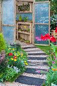 Small green house in backyard flower garden