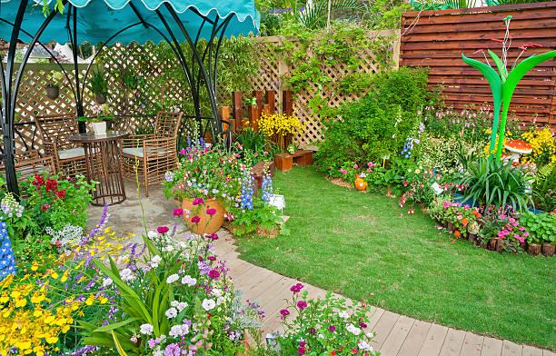innenhof mit dem blumengeschmückten garten - sonnenschirm terrasse stock-fotos und bilder