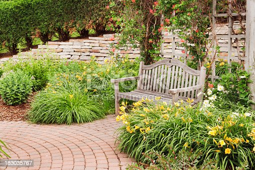 Outdoor patio garden landscaping, featuring a weathered teak wood bench with arbor behind it, brick pavers laid in curved path, flower beds of day lillies and perennials, and a high, dry-laid stone wall, set into a hillside bordered with a hedge. Horizontal view with copy space and no people.