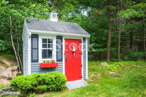 A small shed with a ramp holds, lawnmowers, snow throwers and tools for yard maintenance.