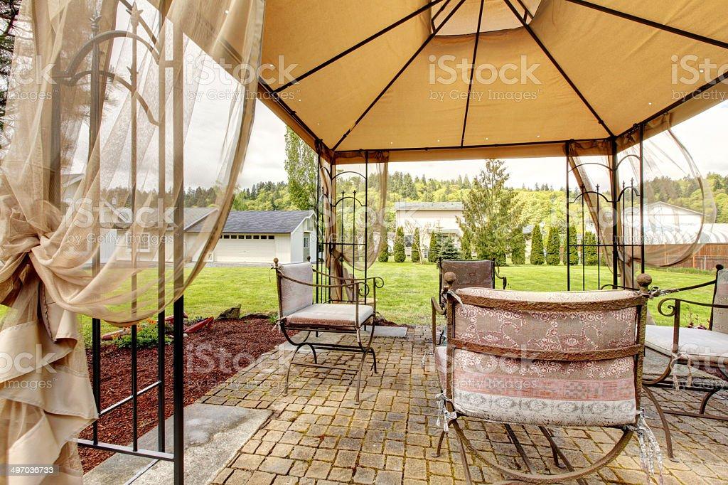 Backyard gazebo with antique chairs stock photo