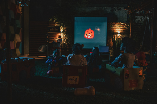 Group of children at backyard movie night. Sitting in cardboard box cars, eating popcorn and watching movie. Social distance during Covid-19 pandemic