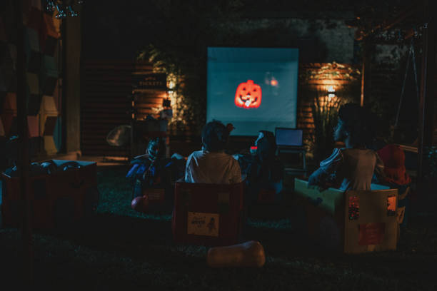 Backyard movie night Group of children at backyard movie night. Sitting in cardboard box cars, eating popcorn and watching movie. Social distance during Covid-19 pandemic halloween covid stock pictures, royalty-free photos & images