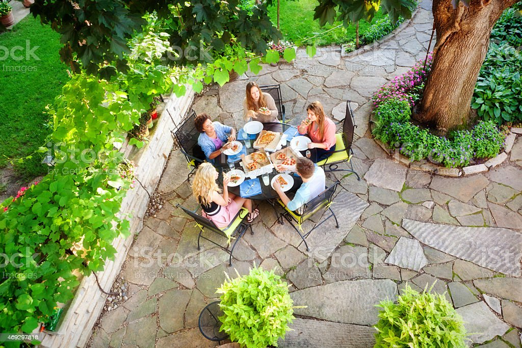 Backyard Patio, Landscaping And Garden With Teenagers Enjoying Pizza  Royalty Free Stock Photo