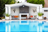 Backyard patio of a luxury residence with swimming pool and fireplace under diffuse daylight.