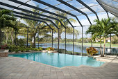 A backyard pool located in a tropical setting covered by a screen lanai. Lake in behind.