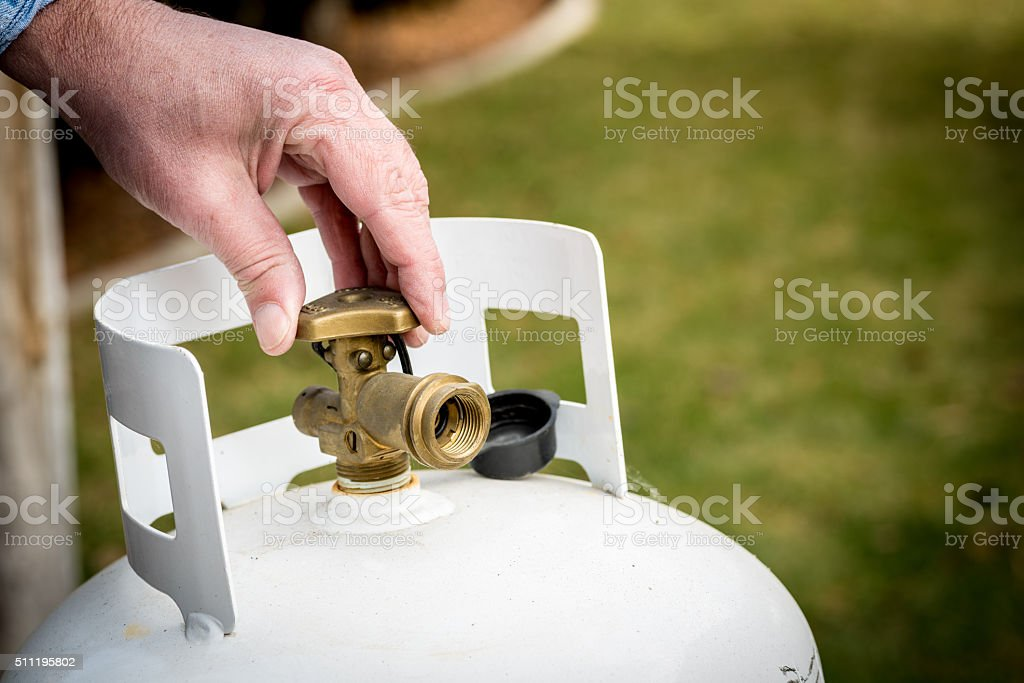 Backyard propane tank valve adjustment stock photo