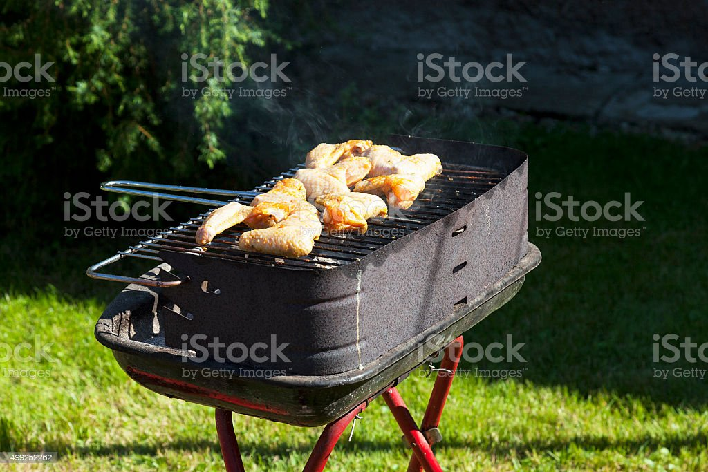 Backyard Summer barbecue grill with smoking grilled chicken .