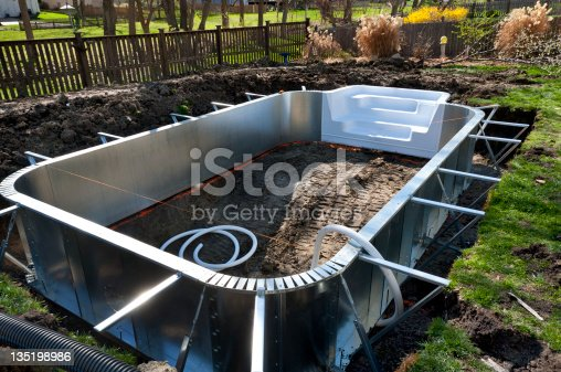 Aluminum sides and support beams are laid out in an excavation during a suburban home swimming pool installation project.