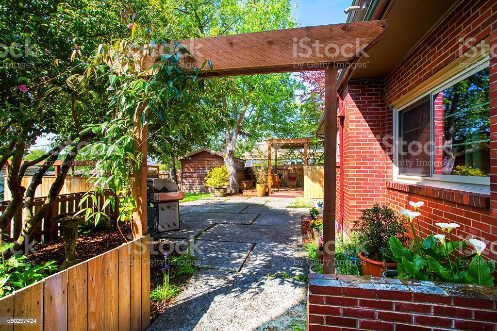 Backyard view. Entrance to garden and patio area Стоковые фото Стоковая фотография