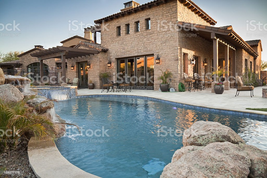 Backyard view of luxury home with swimming pool stock photo