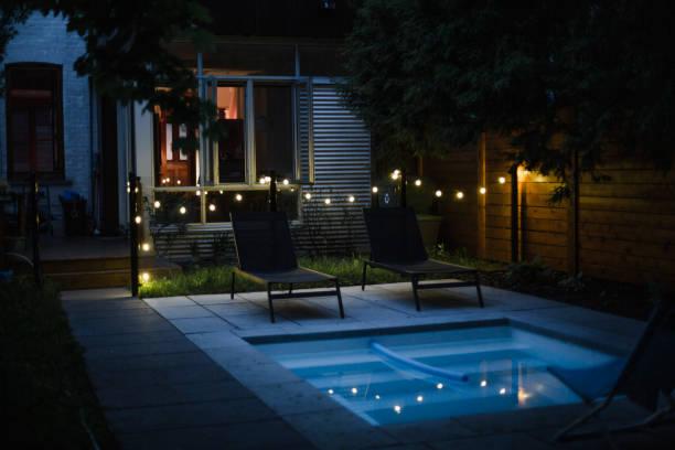 Backyard with swimming pool at night stock photo