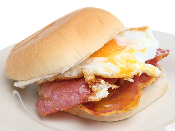 A bacon and egg breakfast sandwich on a white plate stock photo