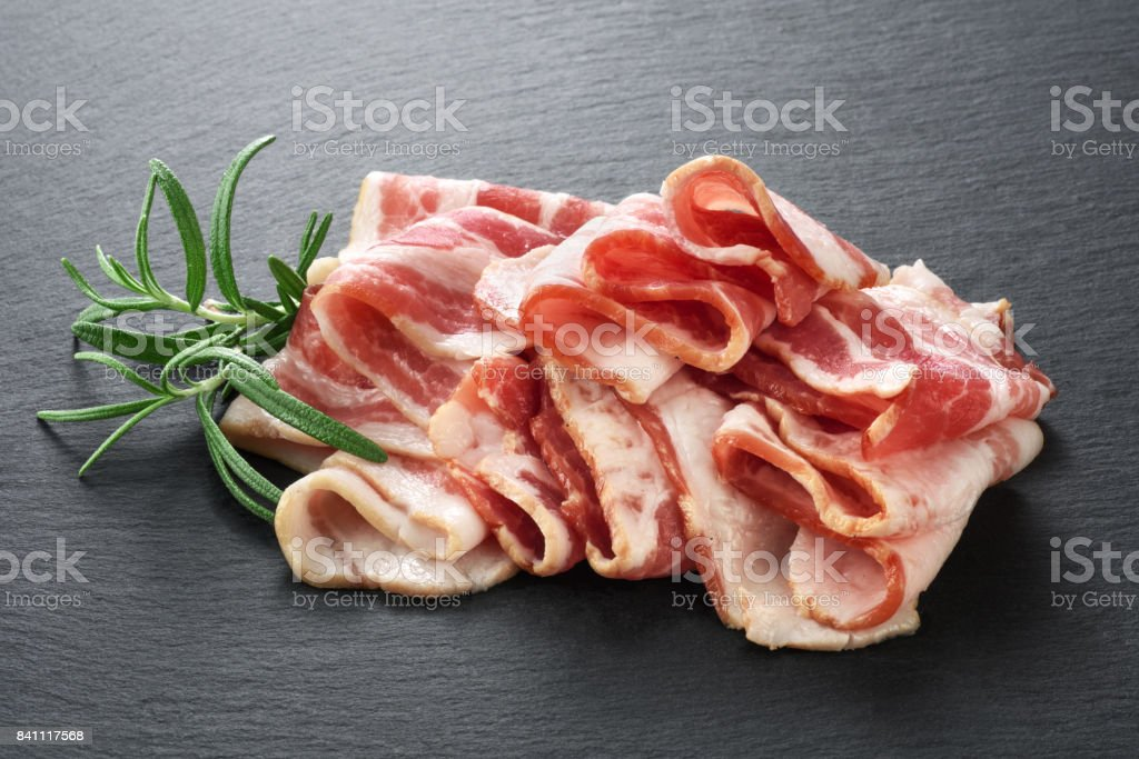 Bacon and rosemary on the background of a slate board stock photo