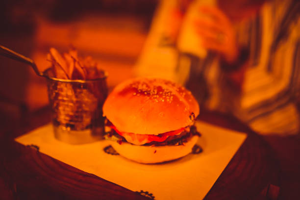 a bacon, cheese, chicken, beef burger with potato fries, wedges, wafers. with warm light and smooth background. - burger and chicken zdjęcia i obrazy z banku zdjęć