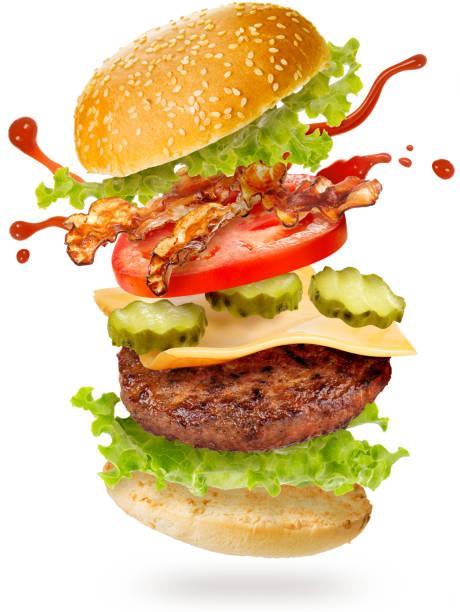 bacon cheeseburger fliegen auf weißem hintergrund - gemüselaibchen stock-fotos und bilder
