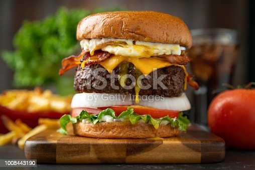 A bacon cheeseburger with fried egg, and all the trimmings. Commercial lighting.