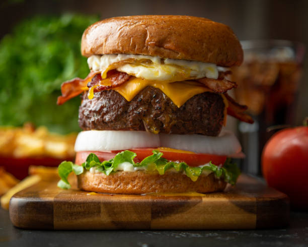 Bacon Cheeseburger with Fried Egg- Moody A bacon cheeseburger with fried egg, and all the trimmings. Moody lighting. bacon cheeseburger stock pictures, royalty-free photos & images