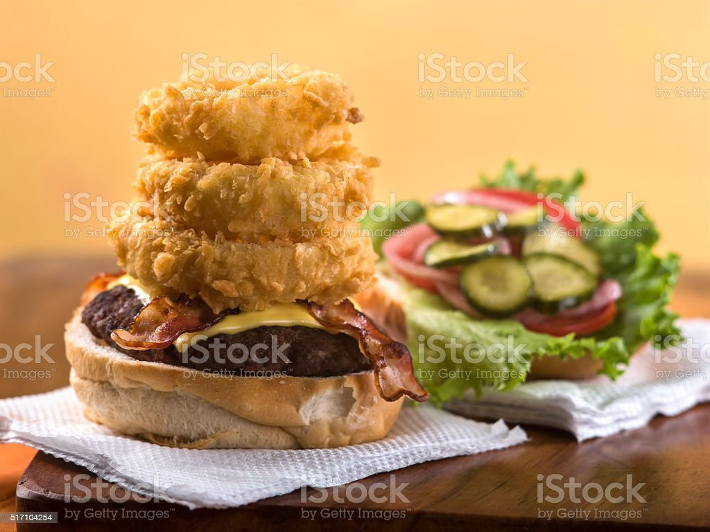 Bacon Cheeseburger with stack of Onion rings stock photo