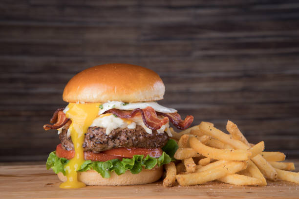 Bacon Egg Burger Fresh bacon egg burger with french fries bacon cheeseburger stock pictures, royalty-free photos & images