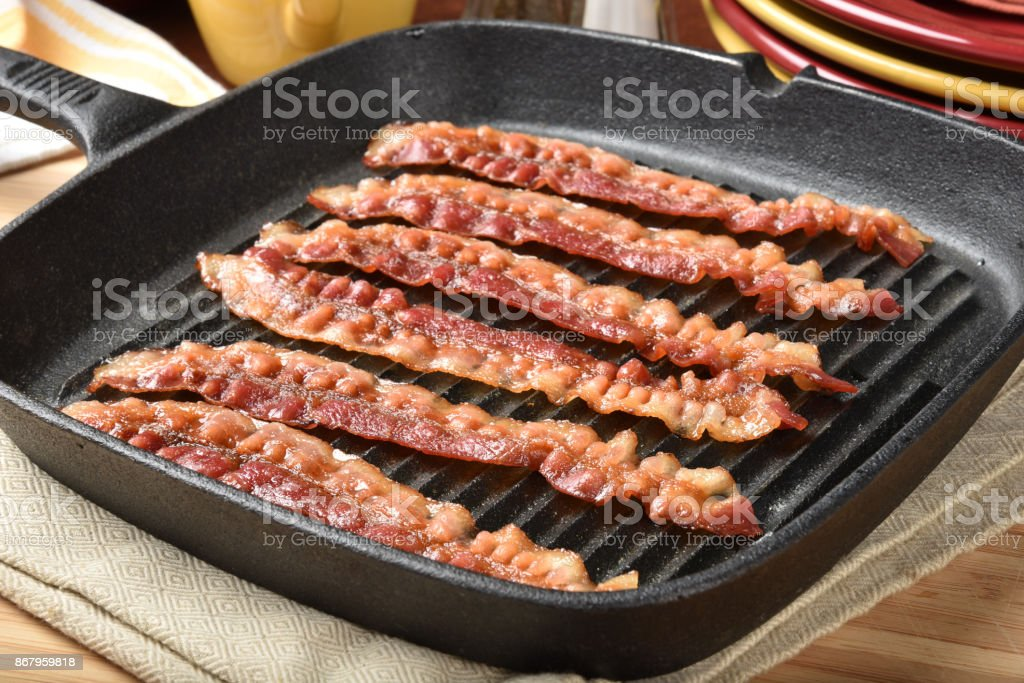 Bacon in a cast iron skillet stock photo