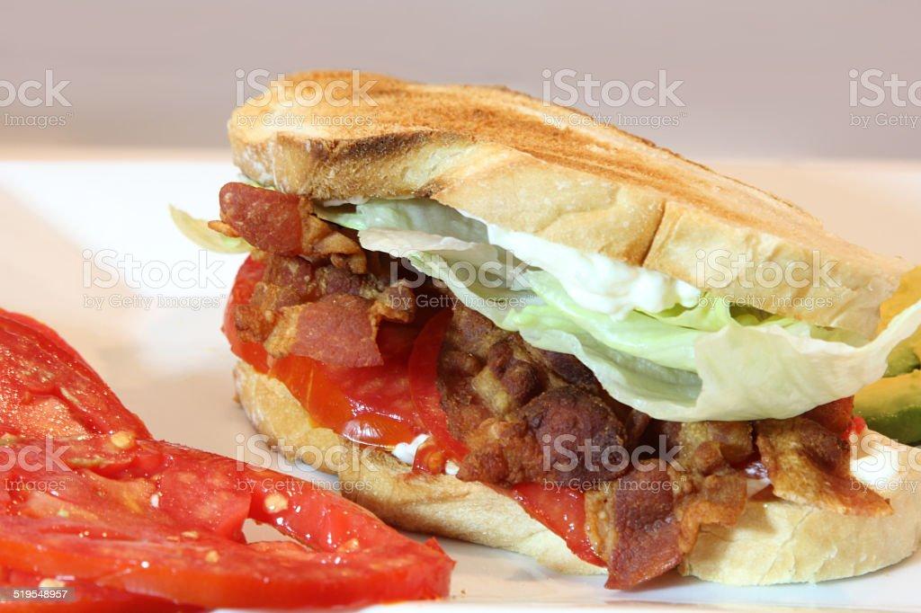 Bacon, lettuce, tomato and avacado sandwich on toasted bread. stock photo
