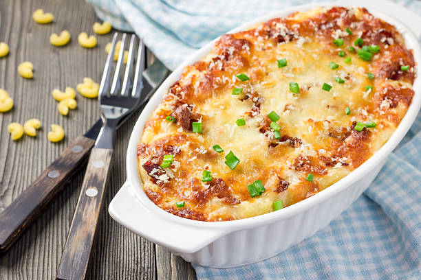 Bacon lovers' mac and cheese in baking dish stock photo