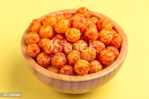 istock Bacon puff balls in wooden bowl on bright colorful background 1077380990
