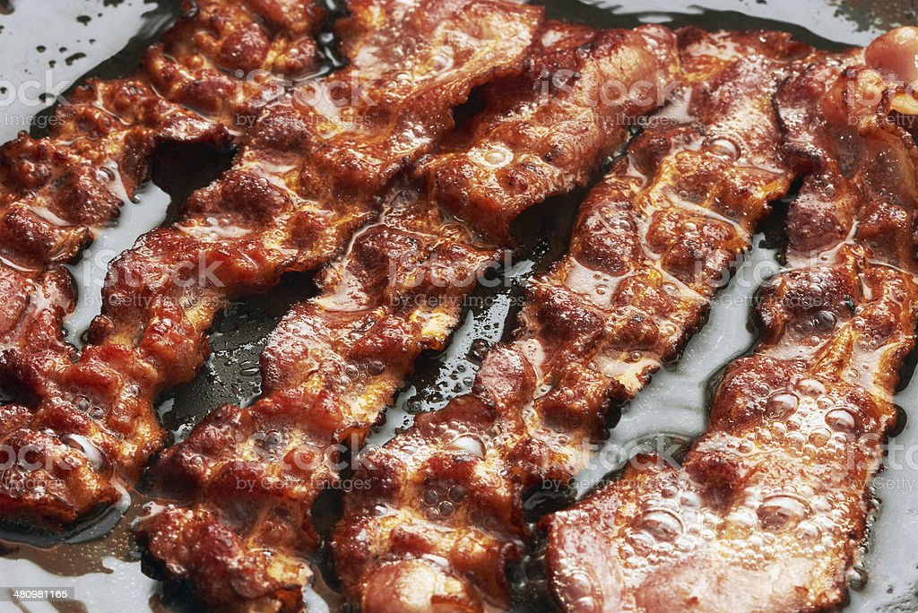 Bacon slice being cooked in frying pan stock photo