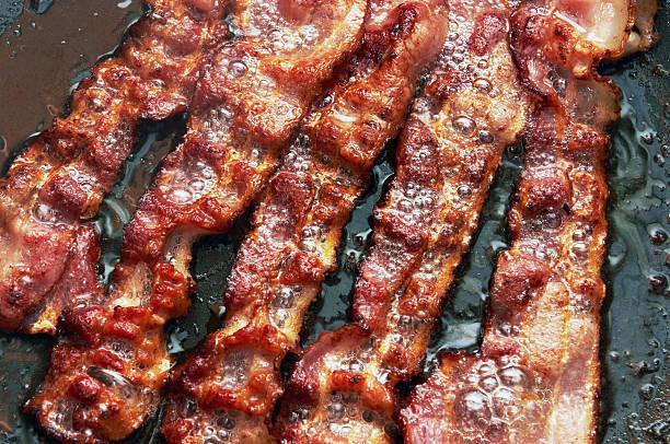 베이컨 절편 중 오븐에서 요리되는 후라이팬 - 베이컨 뉴스 사진 이미지
