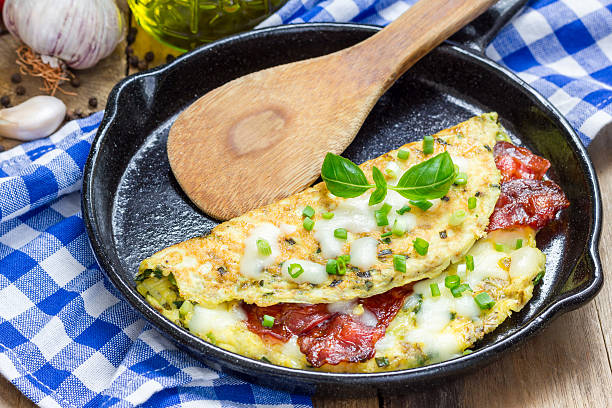 Bacon stuffed omelette on a iron cast pan stock photo