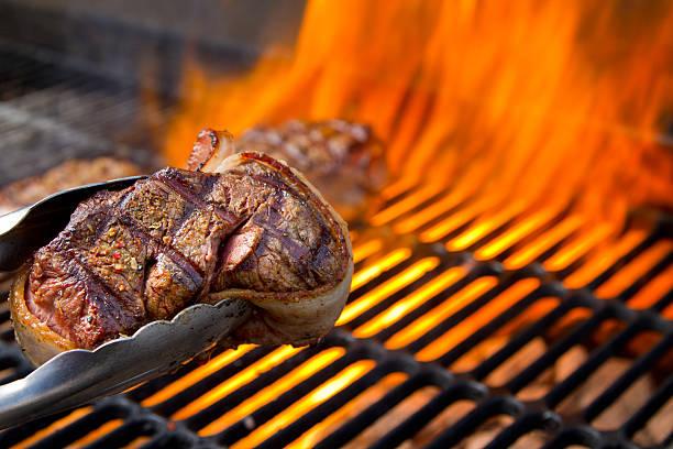 filet mignon im speckmantel rindfleisch auf dem grill mit flammen mit tanz - steak anbraten stock-fotos und bilder