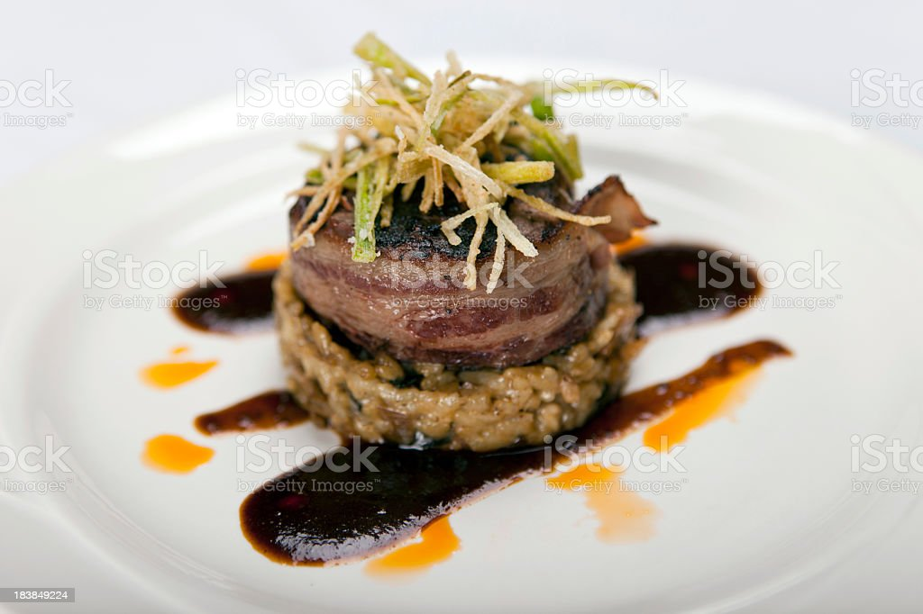Bacon wrapped filet mignon with garnish on white plate royalty-free stock photo