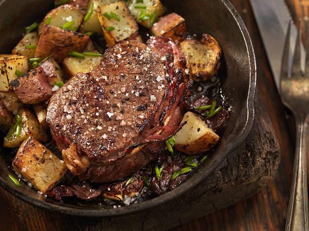 bacon wrapped steak fillets sautéed in garlic butter - knoblauchkartoffeln stock-fotos und bilder