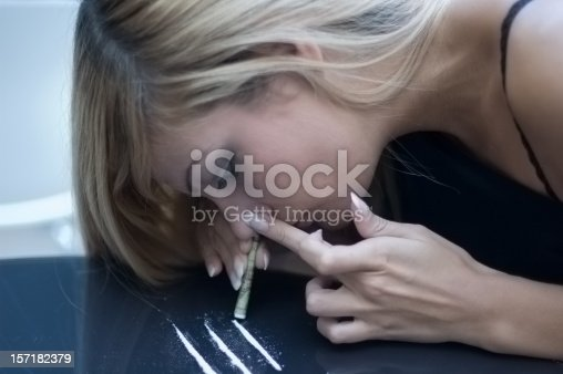 Concept shot of young blonde model snorting drugs, cocaine - in this case crashed suggar.