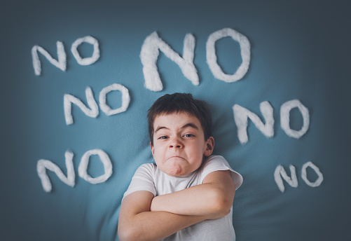Bad boy on blue blanket background. Angry child with no words around.