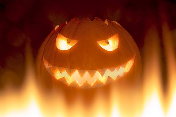 bad carved halloween pumpkin in hot burning hell fire flames - demoniac stock pictures, royalty-free photos & images